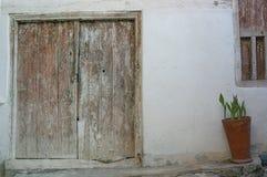 对房子的阴暗的葡萄酒入口:一个木门和门廊与窗口 图库摄影