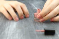 对手和脚的青少年的applaying的指甲油手指 库存图片