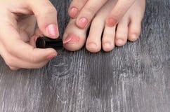 对手和脚的青少年的applaying的指甲油手指 免版税库存照片