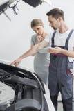 年轻对担心的顾客的修理工作者解释的发动机在车间 免版税图库摄影