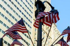 对挥动在风和垂悬一个老时尚大理石大厦的门面的美国国旗行的低透视,庆祝 免版税图库摄影