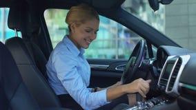 对新的汽车高兴的天真金发碧眼的女人,接触任意按钮,快乐作为孩子 股票录像