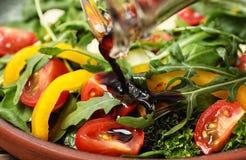 对新鲜蔬菜沙拉的倾吐的香醋在板材 免版税图库摄影