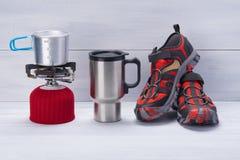 对旅游业,有一个杯子的一个煤气喷燃器对此和红色鞋子,在木轻的背景,有题字的一个地方 库存图片
