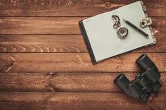 对旅行,双筒望远镜、指南针和笔记本计划在棕色木地板、发现和查寻概念 库存照片