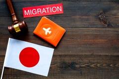 对日本概念的移民 在护照盖子和日本旗子,在黑暗的木背景的锤子附近的文本移民 库存图片