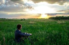 对日落的Buisnessman神色在草 免版税库存图片