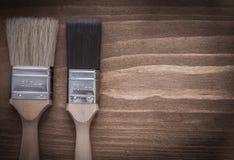 对有木头把柄的油漆刷在木板 免版税库存图片