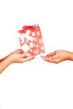 对朋友的手孩子举行礼物红色礼物盒 免版税库存照片