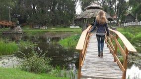 对木树荫处的妇女步行在桥梁通过水槽河在公园 4K 影视素材