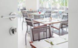 对木桌的被打开的白色门和椅子在餐馆 免版税库存照片