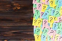 对木背景的许多问题 堆与问号的五颜六色的纸笔记 顶视图拷贝空间 库存照片