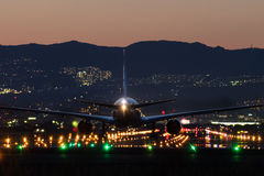 对机场的飞机着陆黄昏的 免版税库存照片