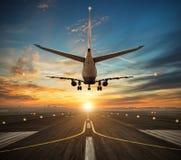 对机场跑道的飞机着陆日落光的 免版税库存照片