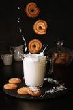 对杯的落的曲奇饼与飞溅的牛奶在黑背景 库存图片