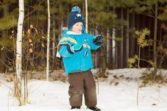 对枝杈散步感兴趣的儿童男孩在一个冬天森林公园 库存图片