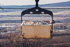 对植物的台车运载的白色石头通过悬索铁路 库存图片