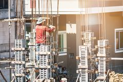 对模板的工作者倾吐的混凝土在建造场所 库存图片