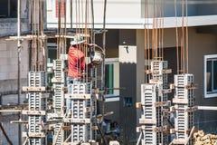 对模板的工作者倾吐的混凝土在建造场所 免版税库存照片