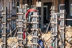 对模板的工作者倾吐的混凝土在建造场所 图库摄影