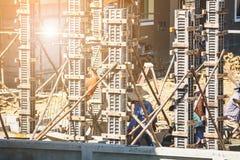 对模板的工作者倾吐的混凝土在建造场所 库存照片