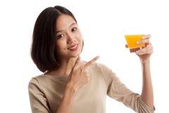对橙汁的年轻亚洲妇女点 免版税库存图片