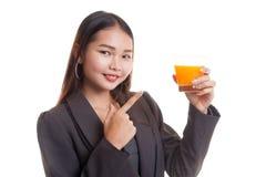 对橙汁的年轻亚洲妇女点 库存照片