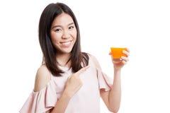 对橙汁的年轻亚洲妇女点 免版税库存照片