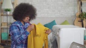 对洗涤做家庭作业的衬衣的非裔美国人的主妇的结果不满意 股票视频