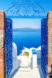 对海和火山的看法通过门,从Fira圣托里尼海岛的首都在希腊 免版税库存图片