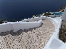 对海滩和深蓝色海, Oia村庄的白色楼梯在圣托里尼海岛,希腊上 库存图片
