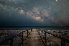 对海滩的木桥走道与银河星系 免版税库存照片
