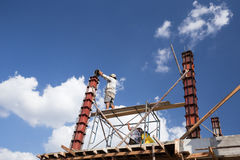 对混凝土桩模子的工作者倾吐的水泥房子建筑的 免版税库存照片
