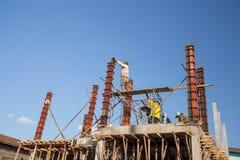 对混凝土桩模子的工作者倾吐的水泥房子construc的 免版税库存图片