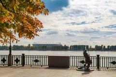 对渔夫的雕塑城市的堤防的新的体育场的背景的建设中温暖的秋天 图库摄影