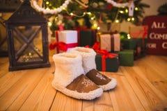 对温暖的家庭鞋子由羊毛制成在与礼物的圣诞树附近在家站立在木地板上 免版税图库摄影