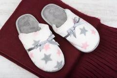 对温暖的拖鞋和红色围巾在白色木背景 图库摄影