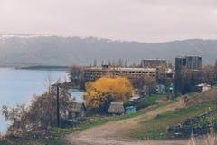 对湖岸的乡下视图与未完成的multy层房子 库存照片