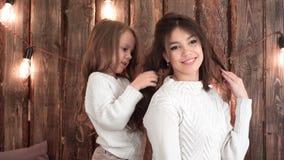 对滑稽的发型做的小女孩她的母亲 免版税图库摄影
