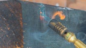 对煤气喷燃器的被烧焦的柴火 库存照片