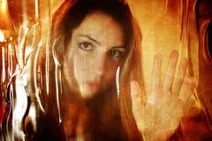 对照片女孩面孔的被抓的作用在肮脏的玻璃后 免版税库存图片