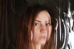 对照片女孩面孔的被抓的作用在肮脏的玻璃后 库存图片