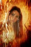 对照片女孩面孔的被抓的肮脏的作用在肮脏的玻璃后 库存图片