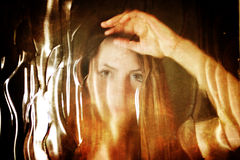 对照片女孩面孔的被抓的肮脏的作用在肮脏的玻璃后 免版税库存图片