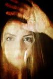 对照片女孩面孔的被抓的肮脏的作用在肮脏的玻璃后 图库摄影