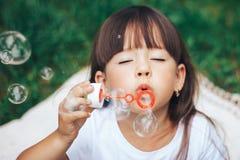 对照相机关闭的小女孩吹的泡影  免版税库存图片