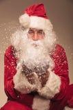 对照相机的圣诞老人吹的雪 库存照片