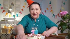 对照相机的愉快的资深妇女藏品蛋糕,当庆祝与她的家庭的生日通过录影闲谈时 股票视频