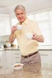对照相机的老人提供的杯子 库存图片