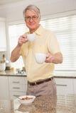 对照相机的老人提供的杯子 免版税库存图片